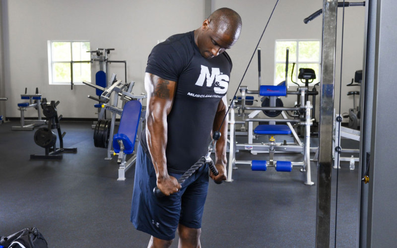 M&S model doing rope tricep pushdowns in gym.