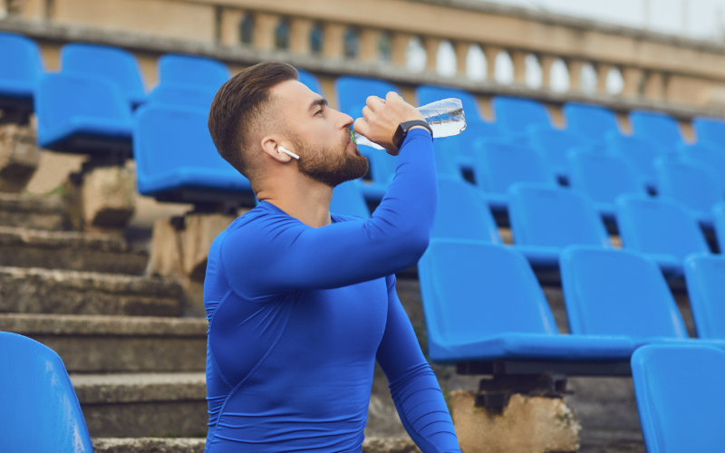 Man drinking water outside in a stadium.