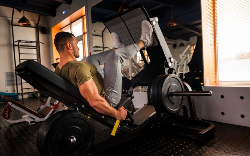 Man doing leg press in gym.
