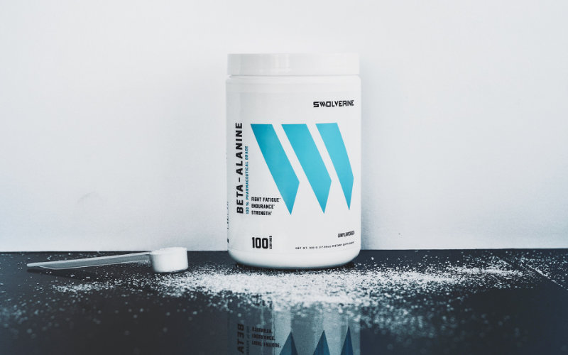 Styled Swolverine Beta-Alanine product shot with beta-alanine bottle in front of white wall and sitting on black reflective surface.