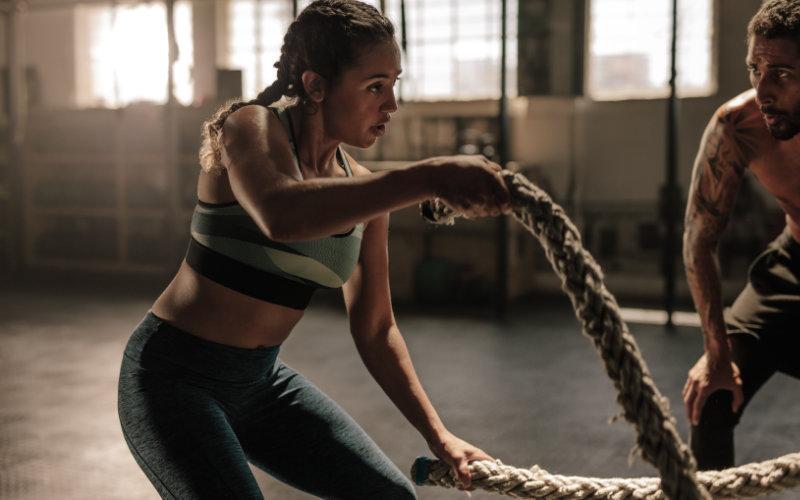 Woman doing battle ropes in gym setting with man cheering her on.