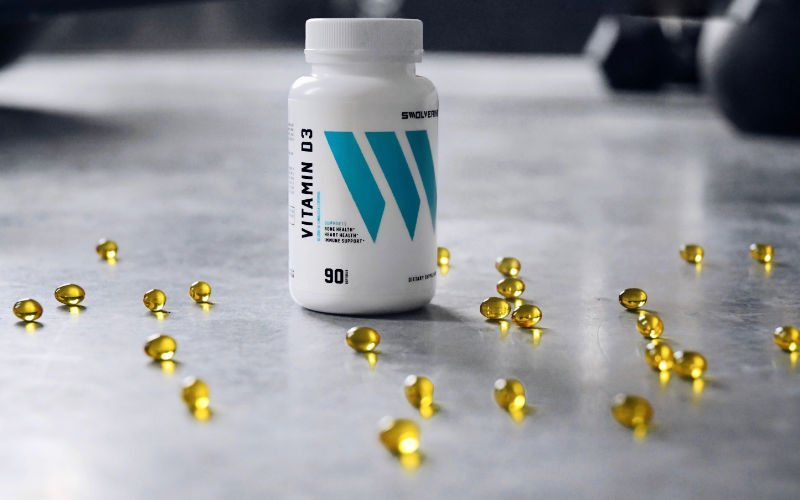 Swolverine D3 bottle sitting on grey counter with gel capsules surrounding the bottle.