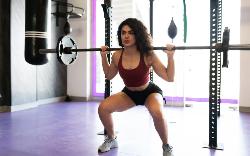 Woman doing barbell back squats in gym.