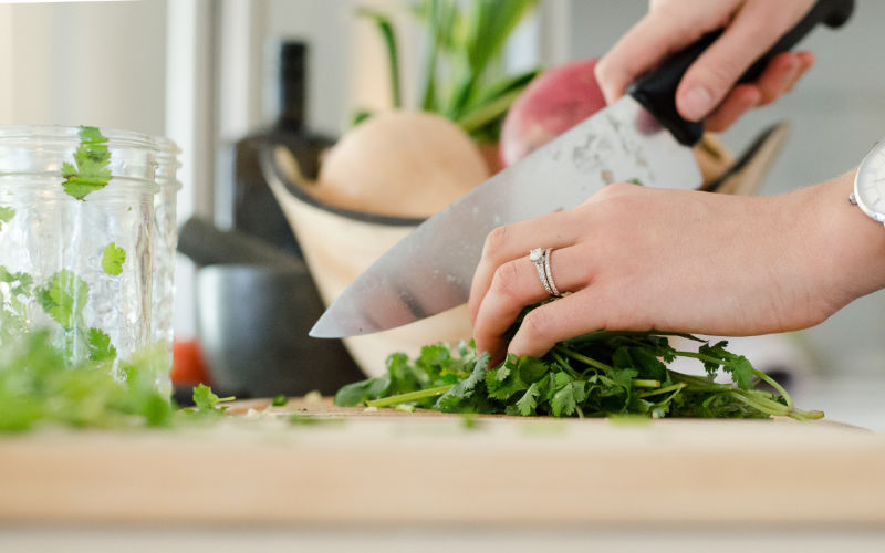 Close up of woman's hands as she chops cilantro on a wooden cutting board.