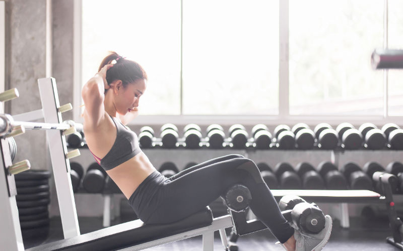 Woman doing decline sit ups in gym.
