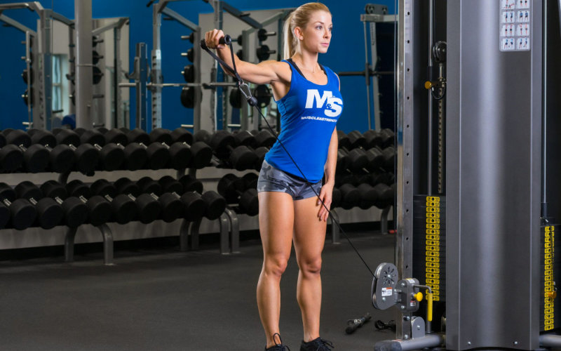 Woman doing cable lateral raises in gym.