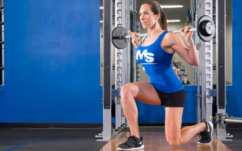 Woman doing barbell lunges in gym.