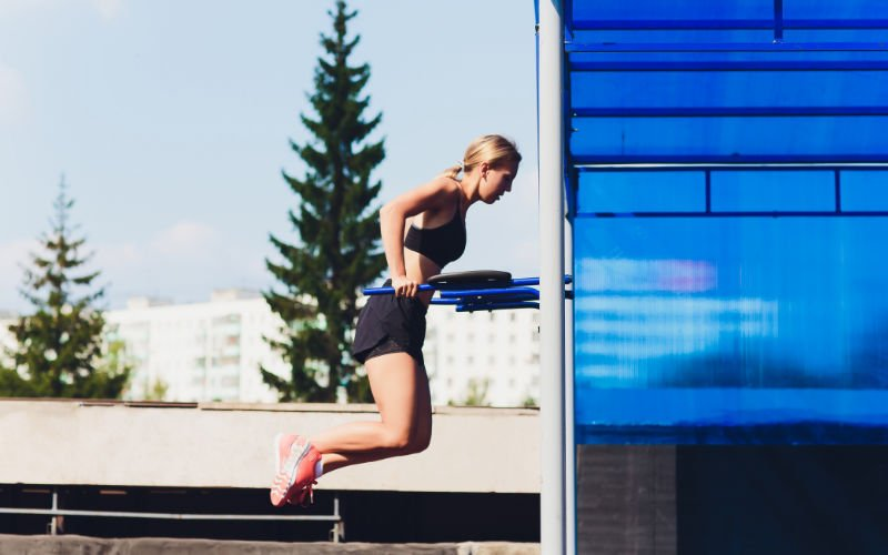Woman doing tricep dips outside in park.