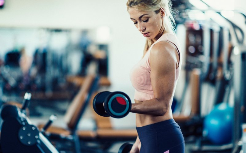 Woman doing single arm dumbbell bicep curls in gym.
