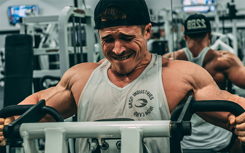 Close up of muscular man doing machine rows in the gym