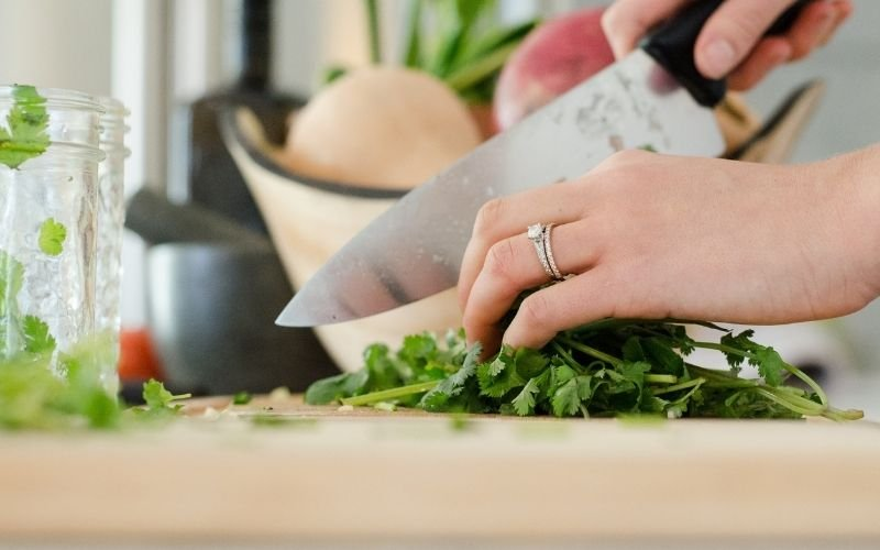 Close up of hand chopping cilantro on kitchen counter