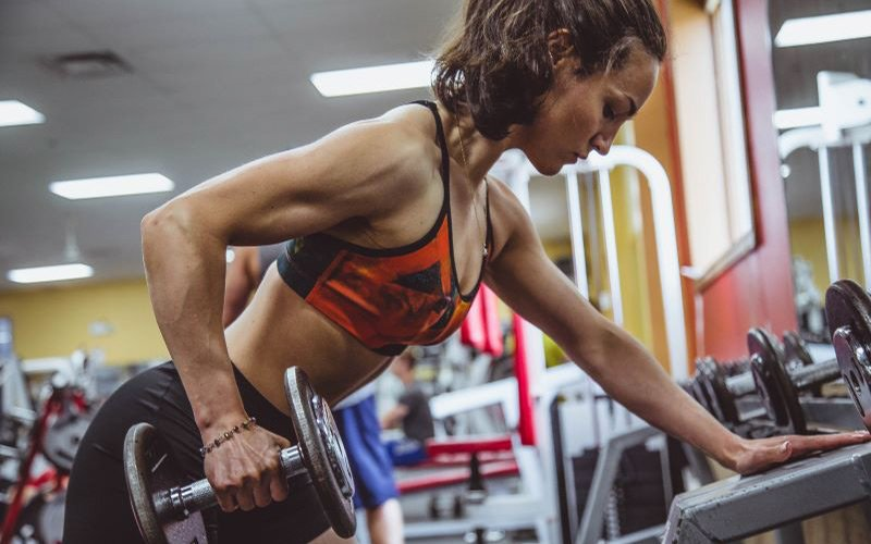 Lean female doing dumbbell rows in a gym