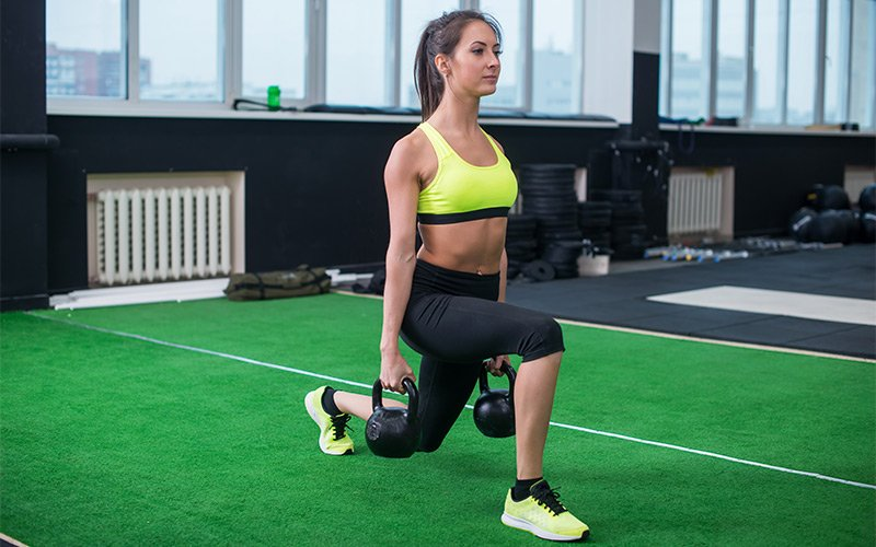 Lean female with brown hair doing kettlebell lunges in the gym.