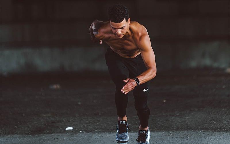 Lean shirtless man running sprints outside