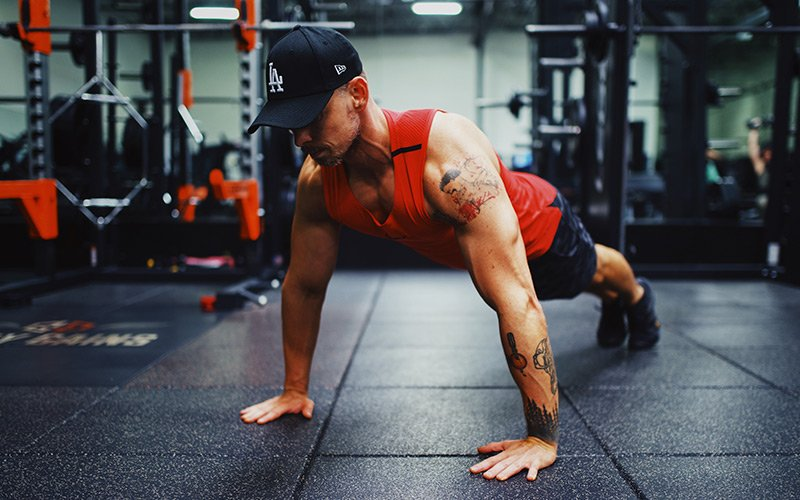 Lean muscular man wearing a red tank top doing a plank in the gym