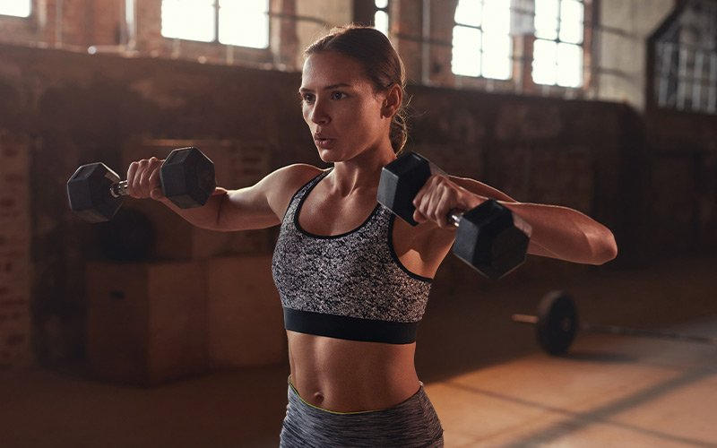 Lean woman with brown hair doing dumbbell lateral raises.