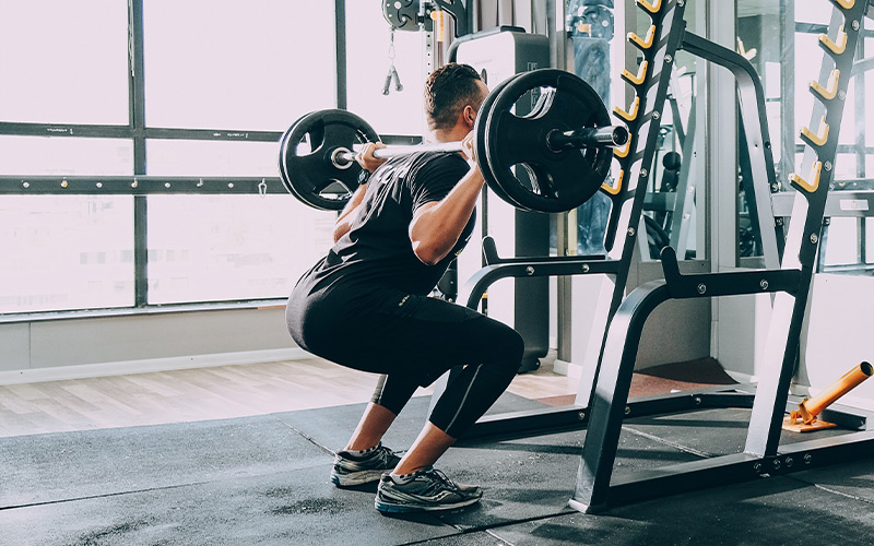 Rear view shot of a man doing barbell squats in the gym