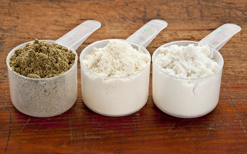 4 Ways To Save Money On A Muscle Building Diet - different scoops of protein
