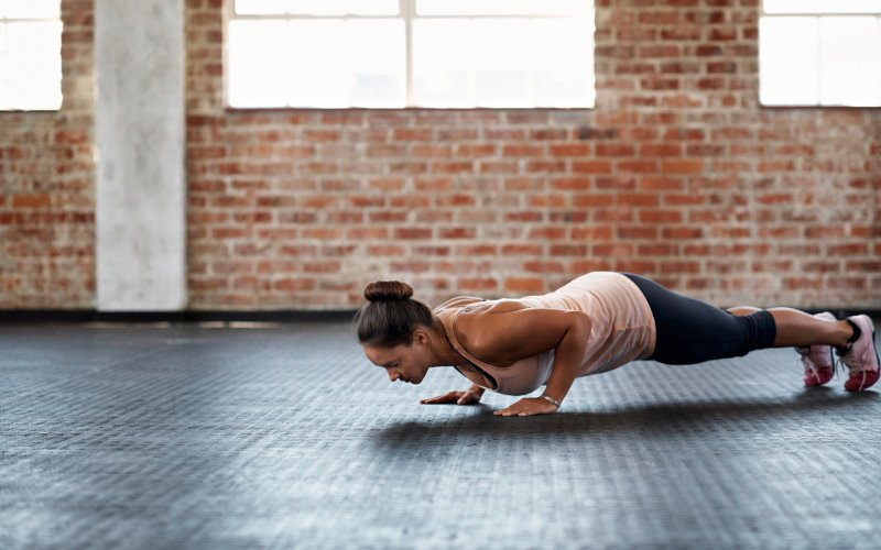 woman does a push-up on the gym floor