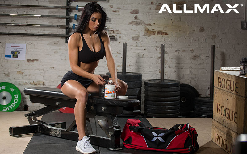 ALLMAX female athlete scooping a fat burning supplment