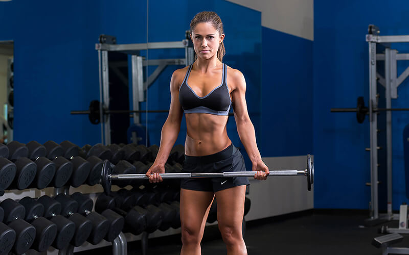 M&S Female Athlete Performing Barbell Curls on Arm Day