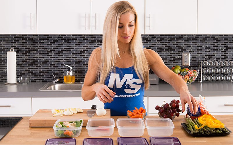 Female Bodybuilder reaching for vegetable and chopping eggs