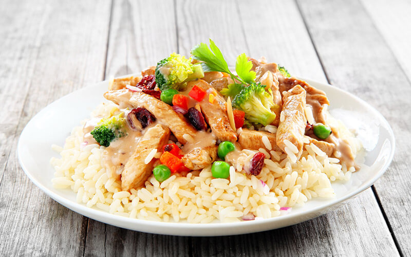 A balanced plate of chicken, veggies, rice, and healthy fats as part of the Zone Diet