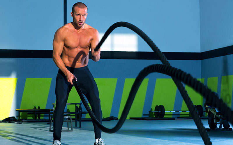 Athlete performing HIIT cardio with battle ropes