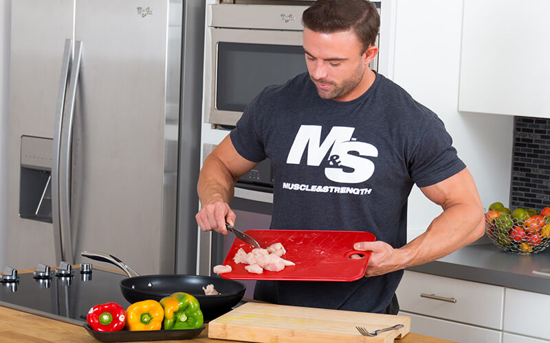 Athlete in M&S Grey Spinal Cooking Chicken and Veggies for Meal Prep