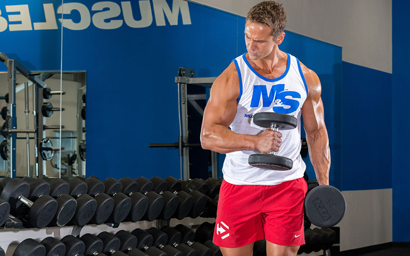 Dymatize Athlete Flexing his tricep while working biceps
