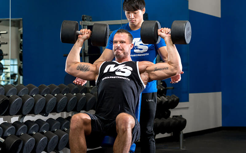 M&S Athlete Performing Dumbbell Shoulder Press With a Spotter