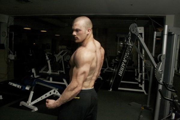 Alex Lee flexing his triceps.