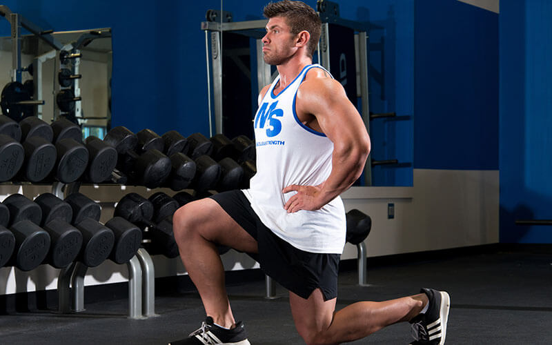 Male athlete performing forward lunges despite knee pain