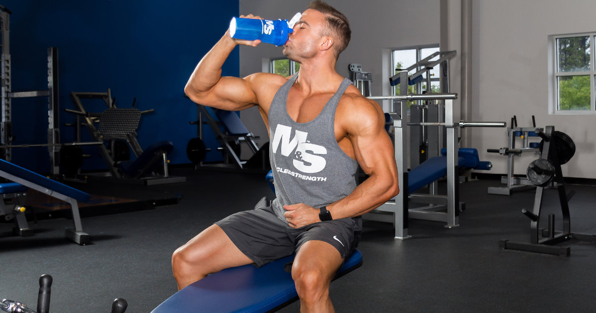 Muscle & Strength athlete in grey M&S tank drinking out of blue M&S shaker.