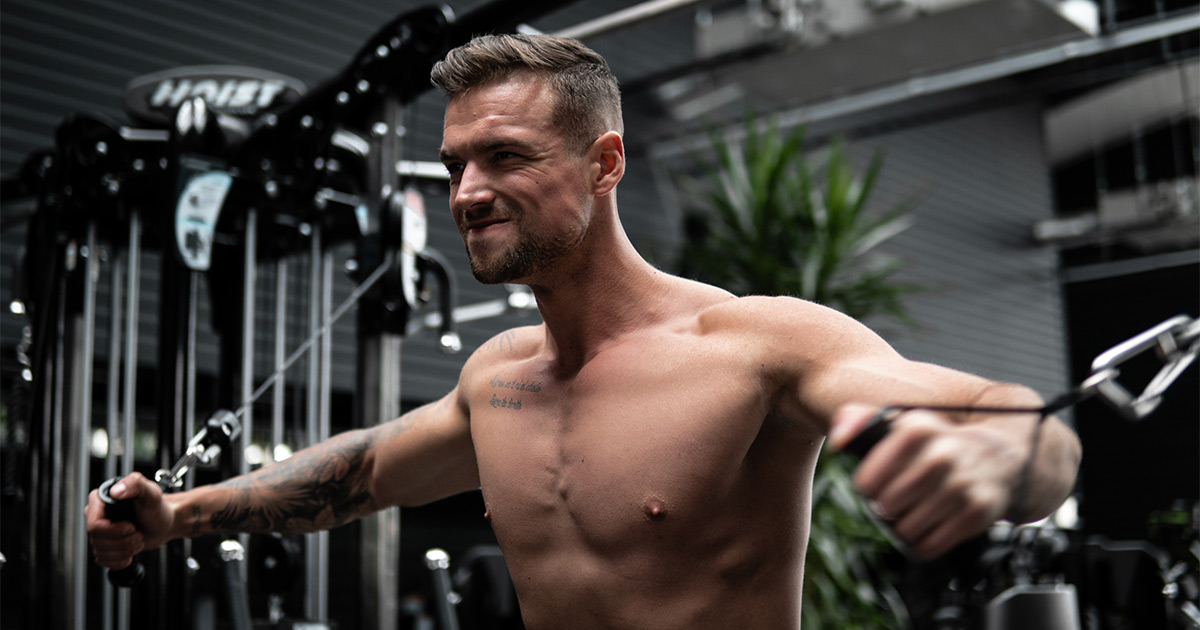 Close up of lean shirtless man doing chest workout in the gym