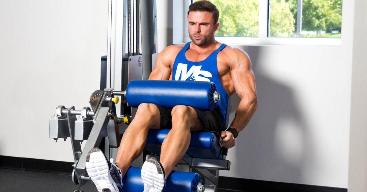 Brett Kahn doing leg curls wearing a Muscle & Strength tank.