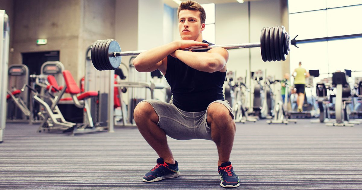 Muscular man doing front squat in the gym