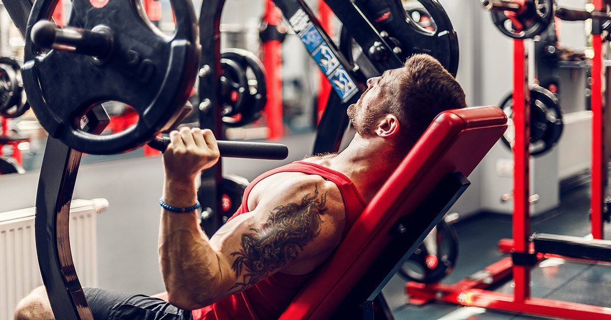 Muscular man using chest press in the gym