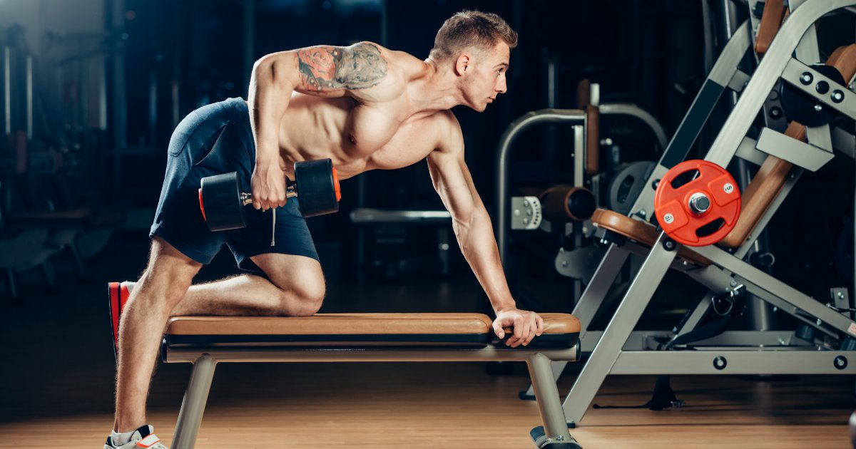 Man doing single arm dumbbell row on flat bench in gym.