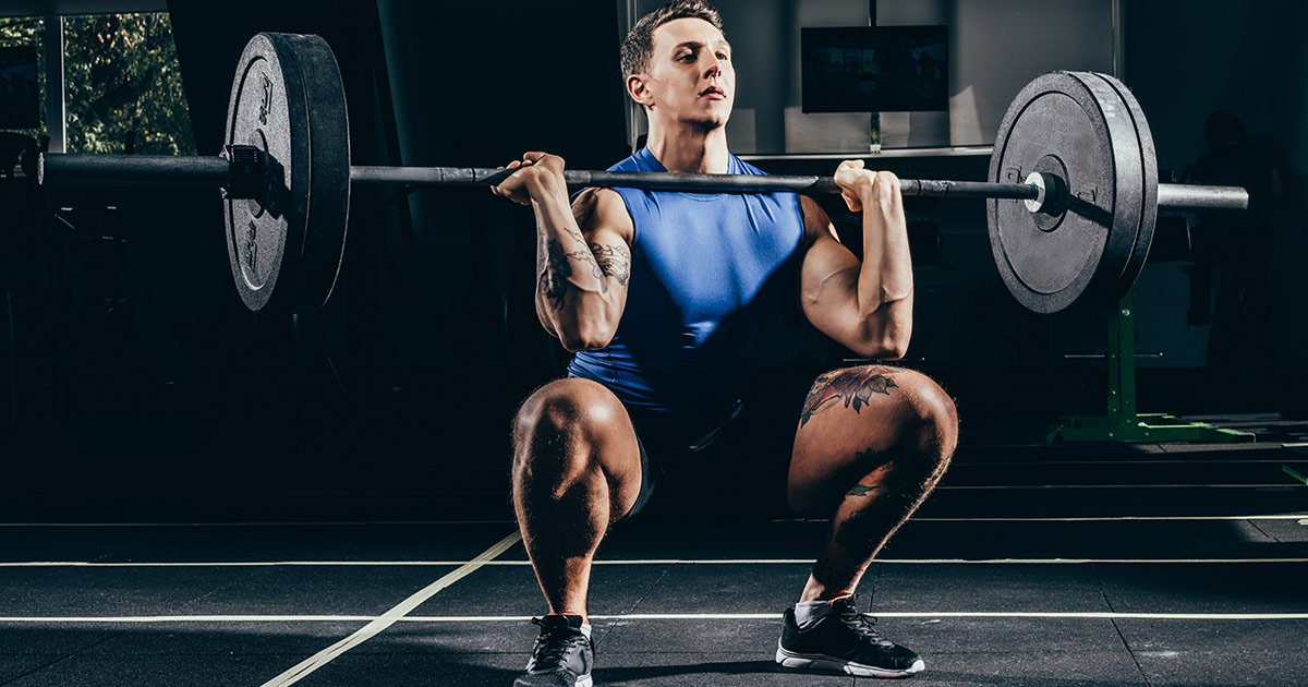 Muscular man doing barbell front squat