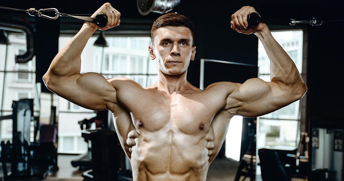 Muscular man shirtless doing bicep curls in the gym