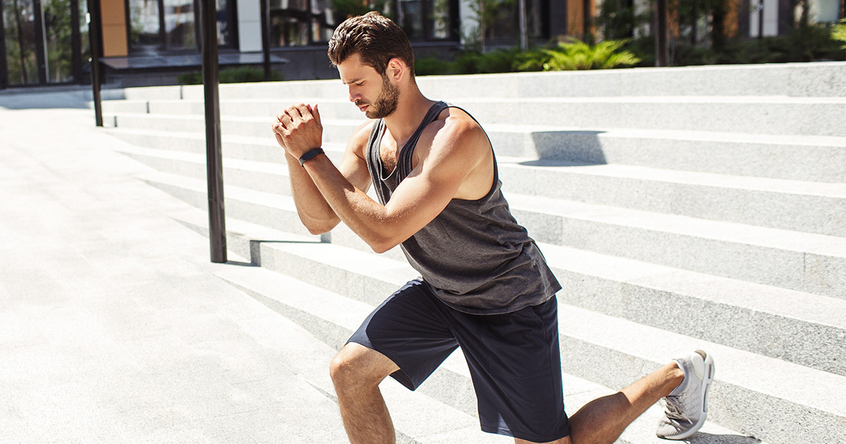 Active man doing bodyweight lunges outdoors in summer period.