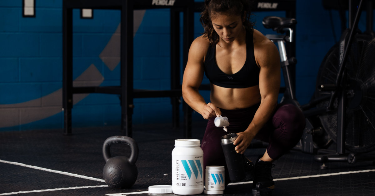 Swolverine athlete scooping whey protein into shaker on floor of CrossFit-style gym.