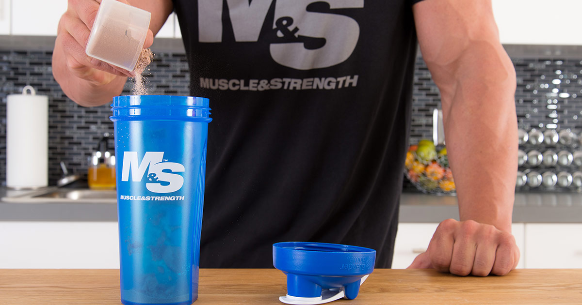 Pouring whey protein into shaker cup