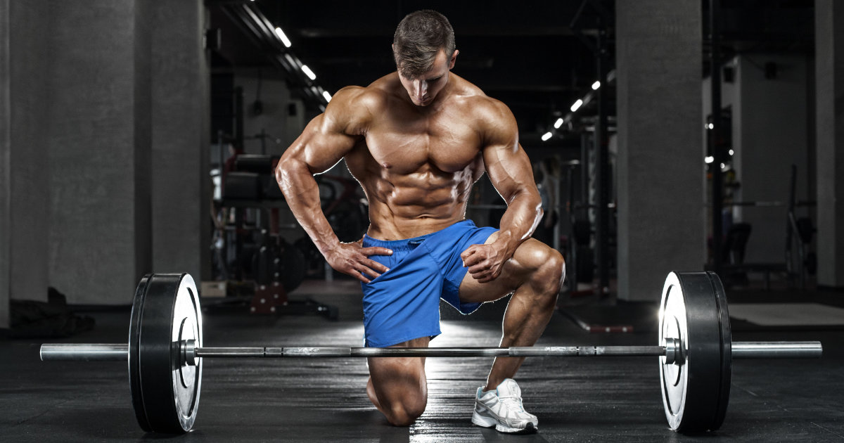 Shirtless, muscular man posing on one knee in front of barbell.