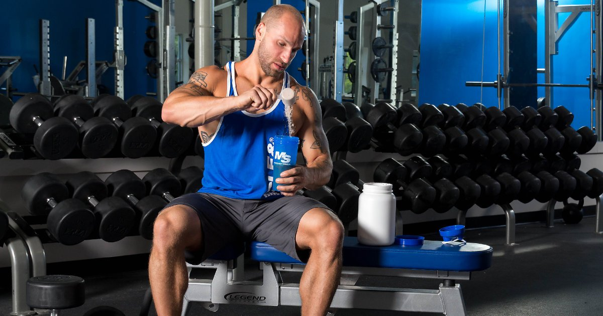 M&S model sitting on bench in gym while scooping protein powder into shaker cup.