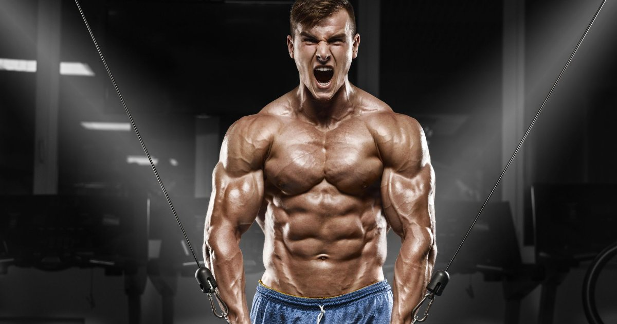 Muscular man doing cable crossover machine.