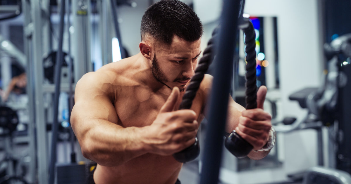 Man doing cable rope tricep pushdowns in gym.