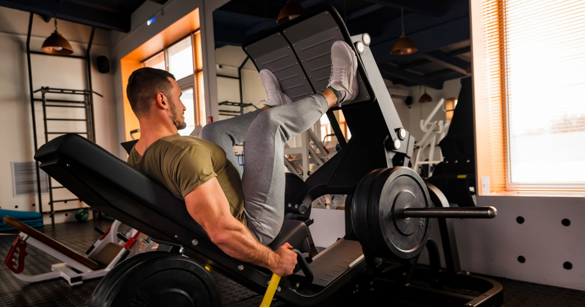 Man doing leg press in gym setting.