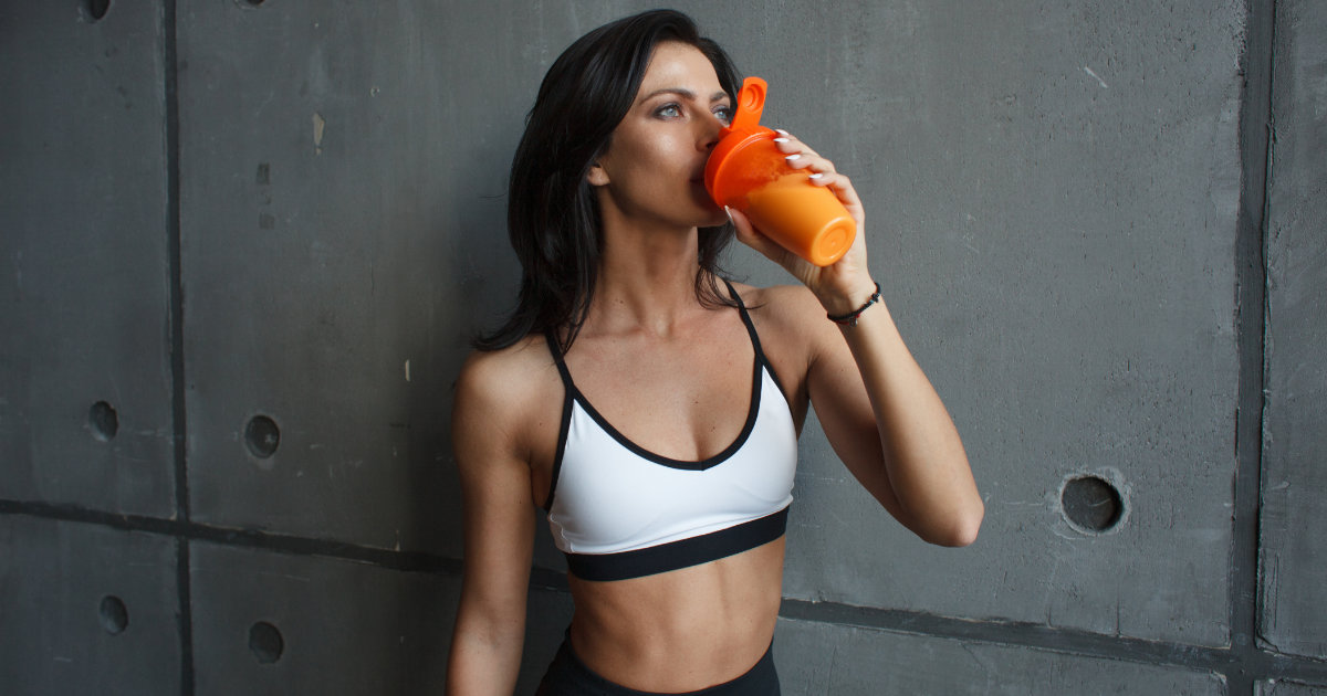 Woman drinking protein shake in front of grey background.